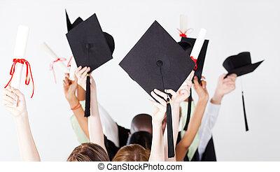 graduation caps and certificate - graduate holding...