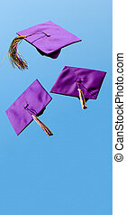 Graduation caps flying in the air after being thrown with room for copy
