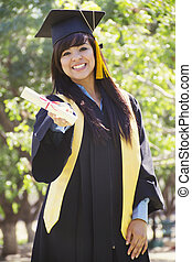 Stock image of happy female graduate, outdoor setting