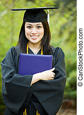 Graduation girl - A happy beautiful graduation girl holding ...