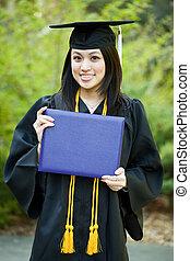Graduation girl - A happy beautiful graduation girl holding...