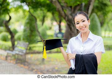 Graduation hat in hand, Happy graduated student girl