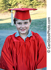 Cute young boy in a graduation cap and gown.