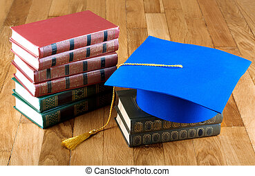 Graduation mortarboard on top of stack of books on wooden...