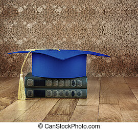 Graduation mortarboard on top of stack of books on a wooden...