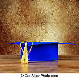 Graduation mortarboard on wooden table on background of...