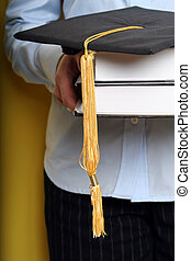 Graduation - A girl holding books and graduation cap