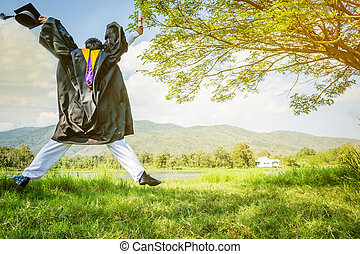 Graduation: Student standing up and jumping holding Graduation certificate with Diploma With background in the nature.