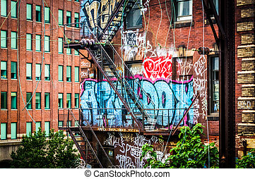 Graffiti and stairs on the side of a brick building seen from the Reading Viaduct, in Philadelphia, Pennsylvania
