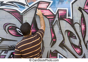 A graffiti artist at work spray painting a brick wall.