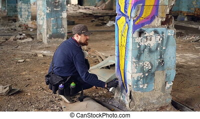 Graffiti artist bearded guy is painting on pillar in...