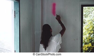 Graffiti artist girl painting on the wall of abandoned...