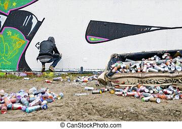 Graffiti Artist - Graffiti artist squatting in front of a...