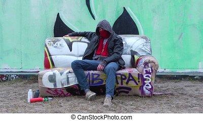 Graffiti Artist on Couch - Graffiti Artist, sitting on a...