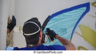 Graffiti artist painting with aerosol spray 4k - Rear view ...