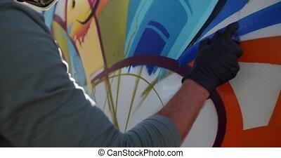 Graffiti artist painting with aerosol spray 4k - Side view ...