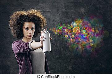 Graffiti artist - Beautiful girl about to draw a graffiti on...
