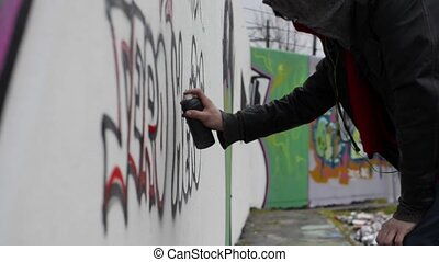 Graffiti Artist - Man, using spray paint to create graffiti...