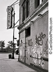 Black and white view of the side of a hotel building with detail of graffiti.