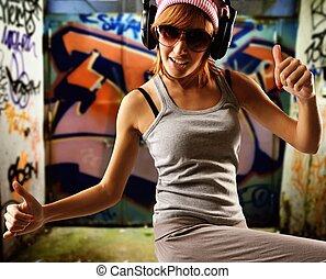 Graffiti painted gateway - Stylish dancing girl against ...