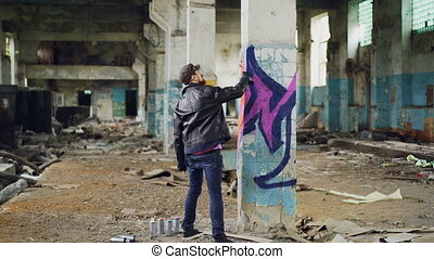 Graffiti painter in casual clothing is drawing with spray paint on column in spacious abandoned building. Abstract images, modern art, creative people and hipsters concept.