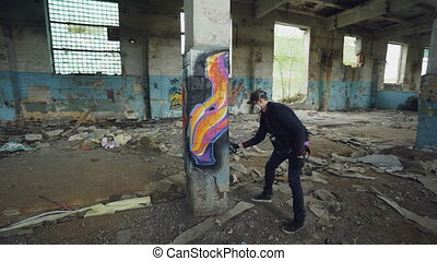 Graffiti painter is protective mask and gloves is drawing on...
