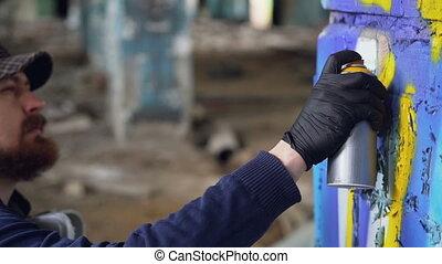 Graffiti painter is squatting near column in old empty...