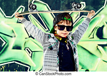 graffiti style - Cool 7 year old boy with his skateboard on...