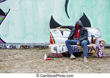 Grafitti Artist posing on a spray painted, old, couch in...
