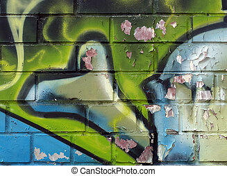Grafitti on a brick wall with peeling paint