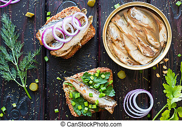 grain bread with sardines and greens next to the bank sprats  on a black background with dill and parsley
