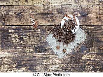 Grain coffee in a cup, which stands on a sackcloth from burlap. Cinnamon on a platter and tied with a rope. Anise stars complement the aroma of coffee. View from above.