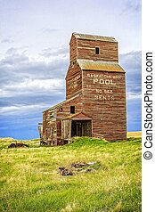 An old brown grain elevator in the ghost town of Bents, Saskatchewan on the Canadian prairies.