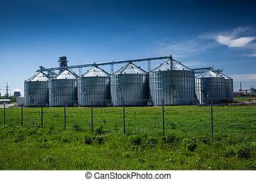 grain elevator at field against deep blue sky