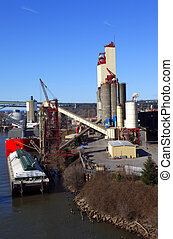 A grain elevator with a parked barge delivering the food product.