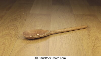 Grain of oats falling on the wooden spoon lying on a wooden surface.