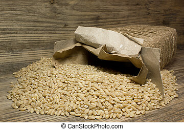 Grain of pearl Barley on a wooden background.