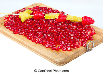 grain of red pomegranate on wooden board