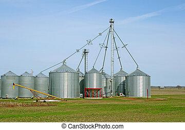 Grain silos on a farm in green spring field.