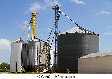 Grain storage elevators and silos for storing harvested crops against a blue sky.