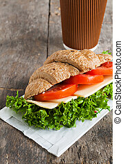 grain vegetarian croissant sandwich and a paper cup of coffee on a wooden background old