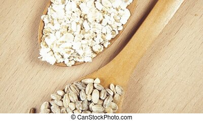 Grains in wooden spoons on wooden background top view -...