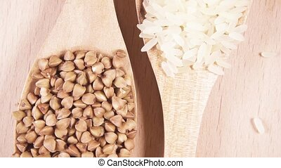 Grains in wooden spoons on wooden background top view