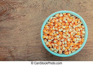 Grains of ripe corn in the bowl on teak wood background .