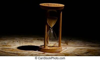 Grains of sand fall down in the hourglass. Spot light -...