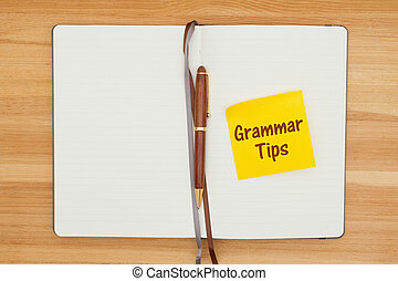 Grammar tips message on sticky note in a journal with a pen