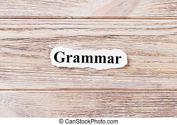 Grammarof the word on paper. concept. Words of Grammar on a wooden background