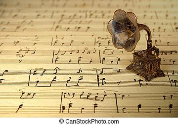Gramophone on old sheet music, retro background