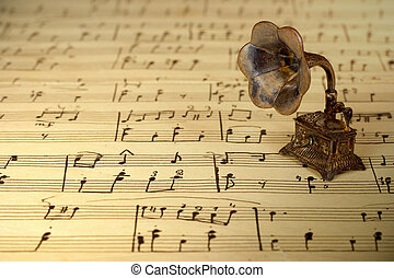 Gramophone on old sheet music, retro background