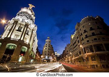 Rays of traffic lights on Gran via street, main shopping street in Madrid at night. Spain.